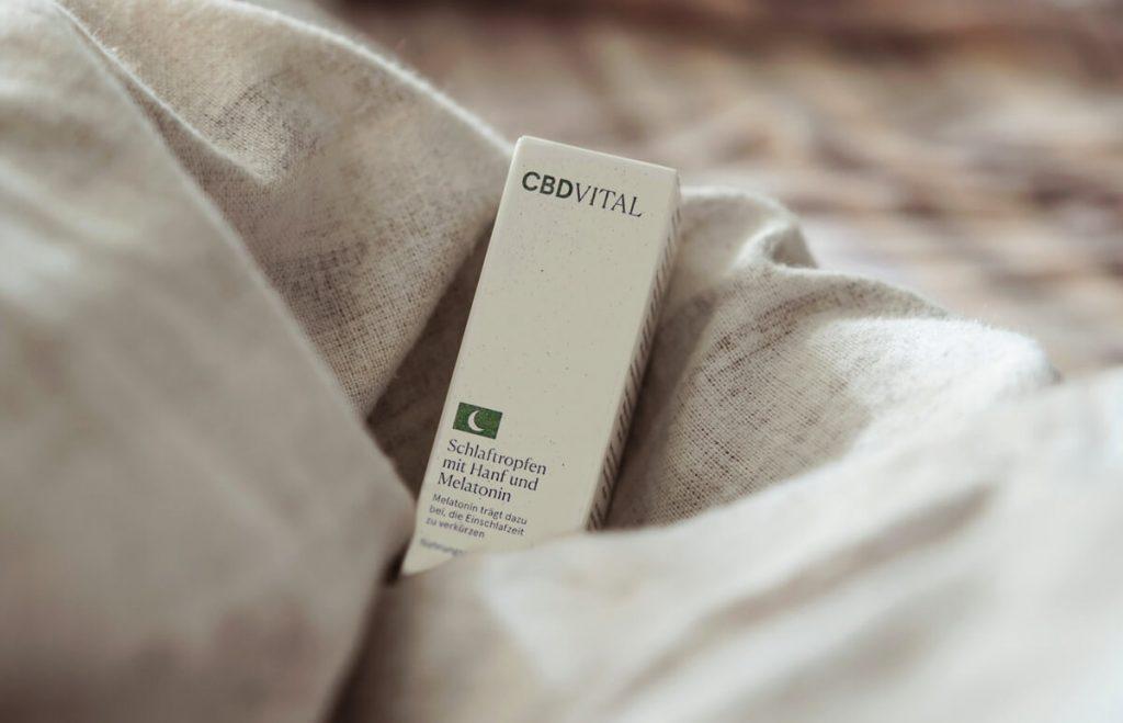 CBD Vital olej na kvalitný spánok s obsahom melatonínu - krabička s olejom položená v prikrývkach