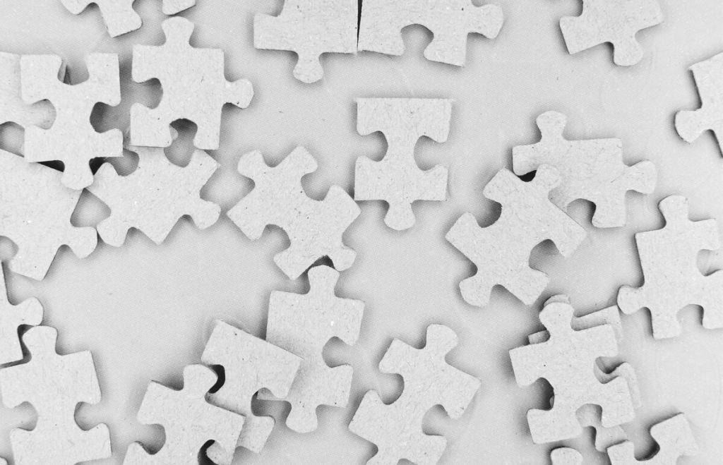 Rozsypané biele kúsky puzzle na bielom pozadí