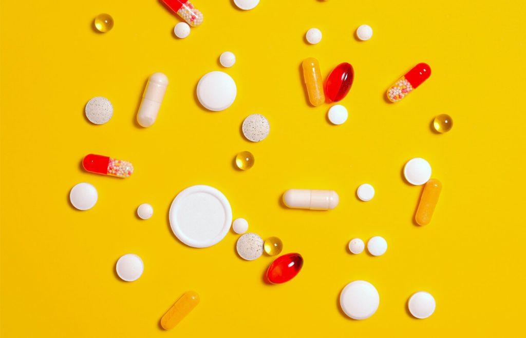 Tablety a kapsule na žltom pozadí