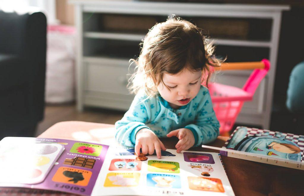 Malé dieťa si listuje v obrázkovej knihe