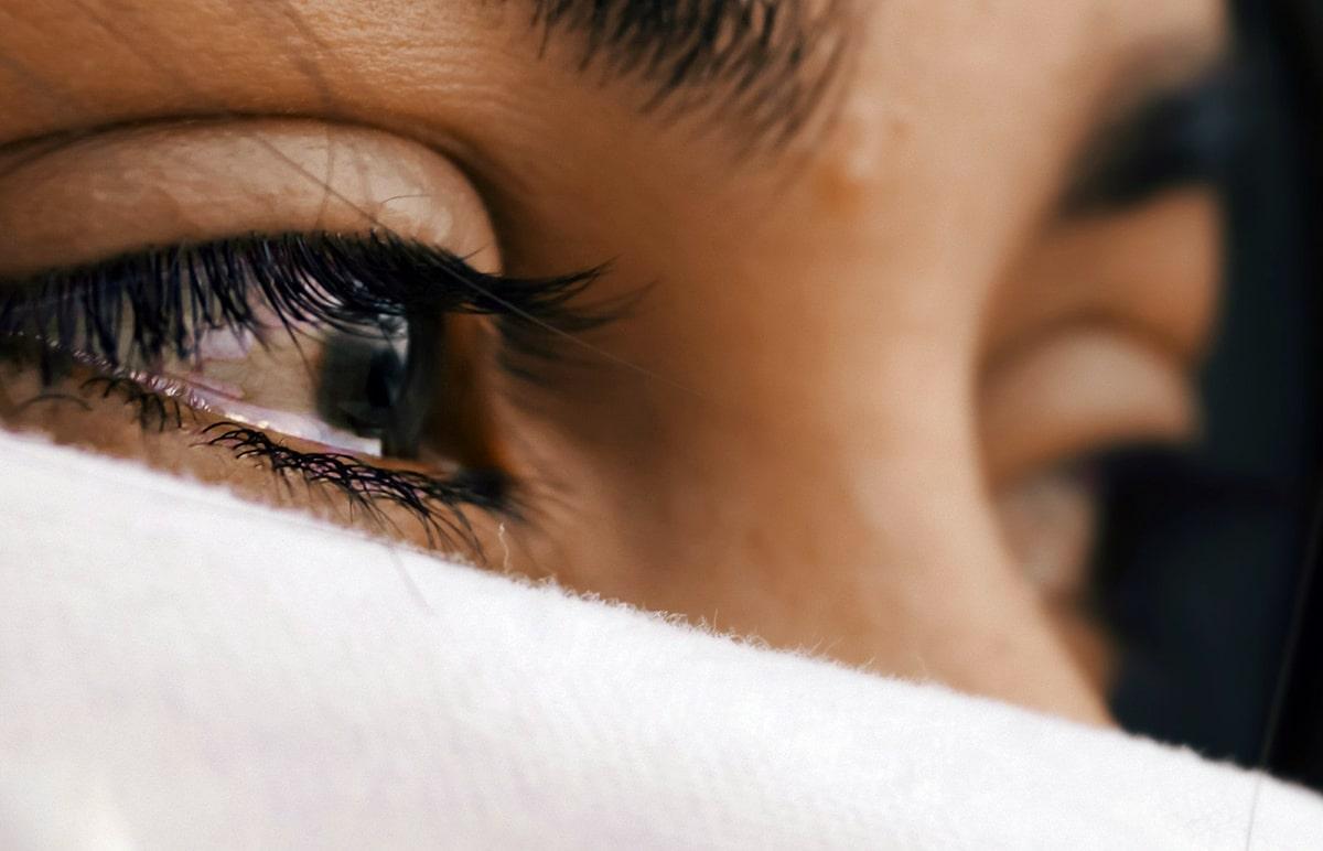 na obrázku je detail oka plačúcej ženy, ktorá má tvár sčasti prekrytú bielou textíliou