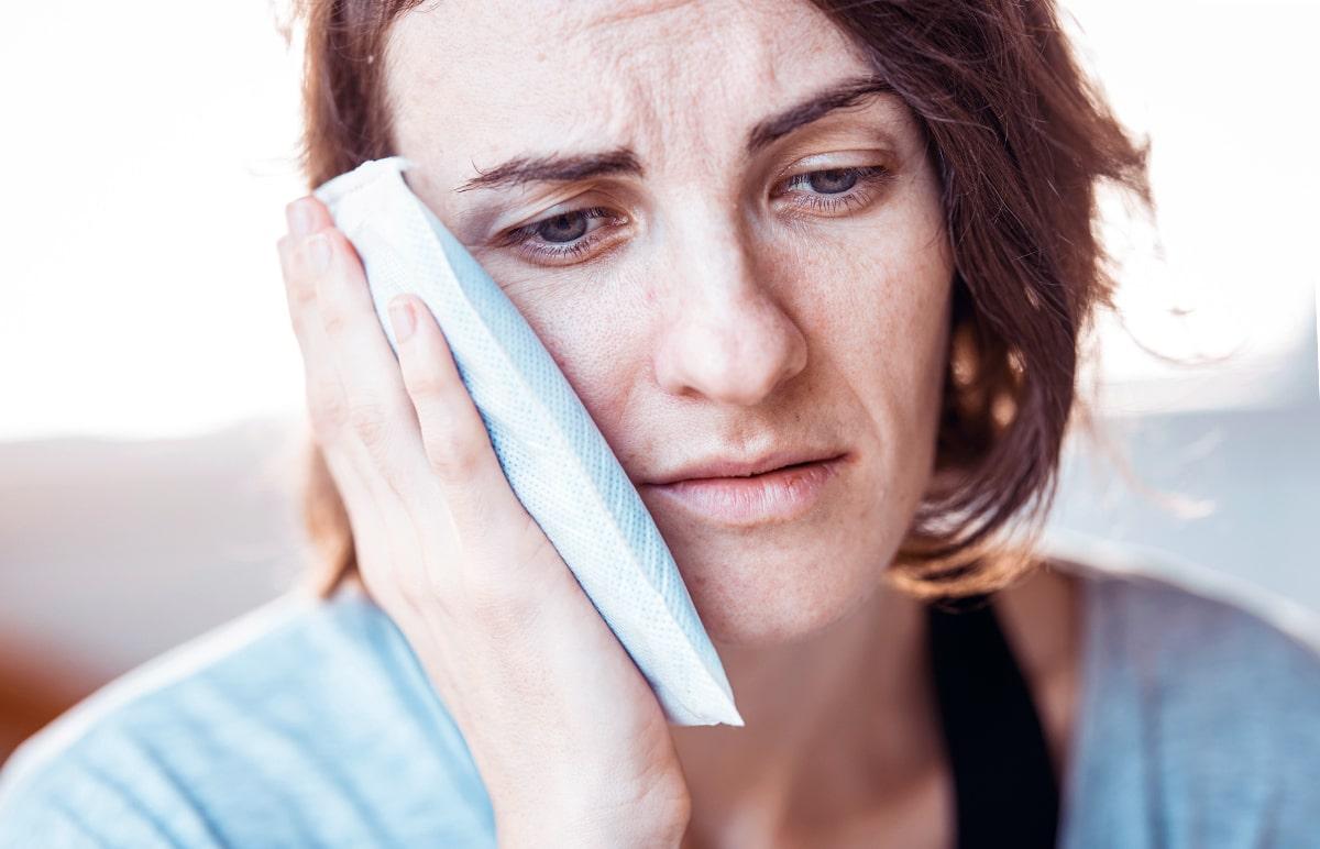 na obrázku je žena, ktorá si drží obklad na sánke proti bolesti zubov