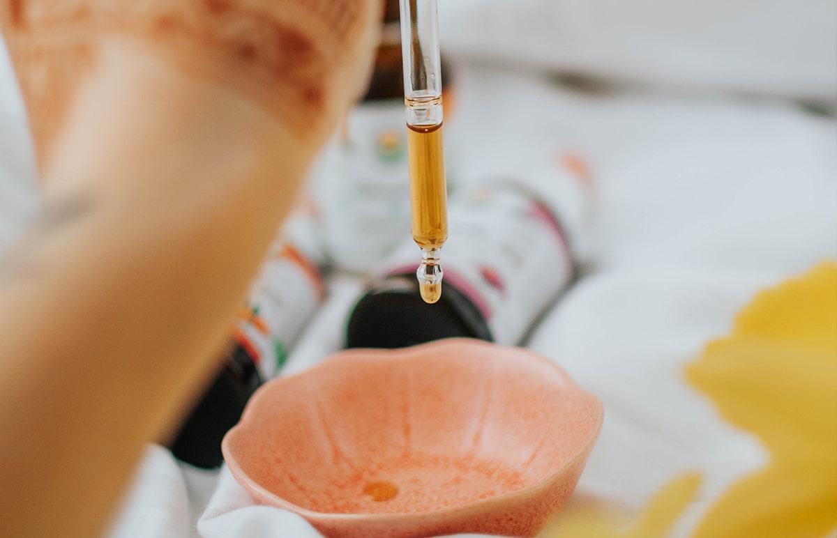 žena drží pipetu a dávkuje cbd olej do misky