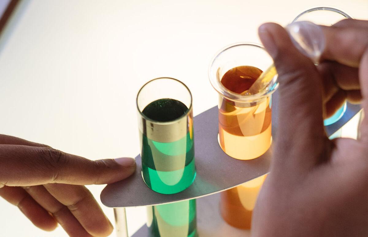 Ilustračný obrázok: testy na drogy: skúmavky s farebným obsahom položené v stojančeku a ruky, jedna ponára do skúmavky testovací papierik